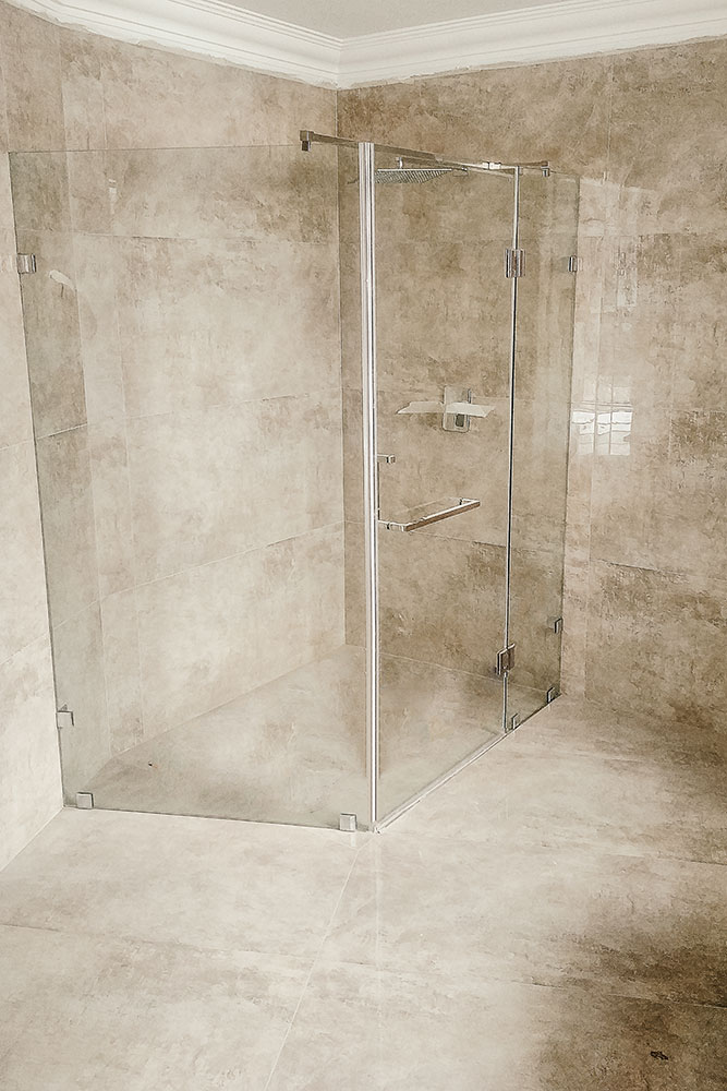 Large brown untiled bathroom with frameless shower