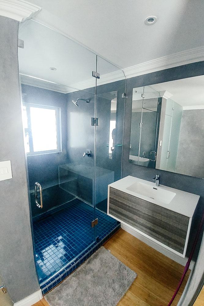 Grey and white bathroom with blue tiled frameless bathroom