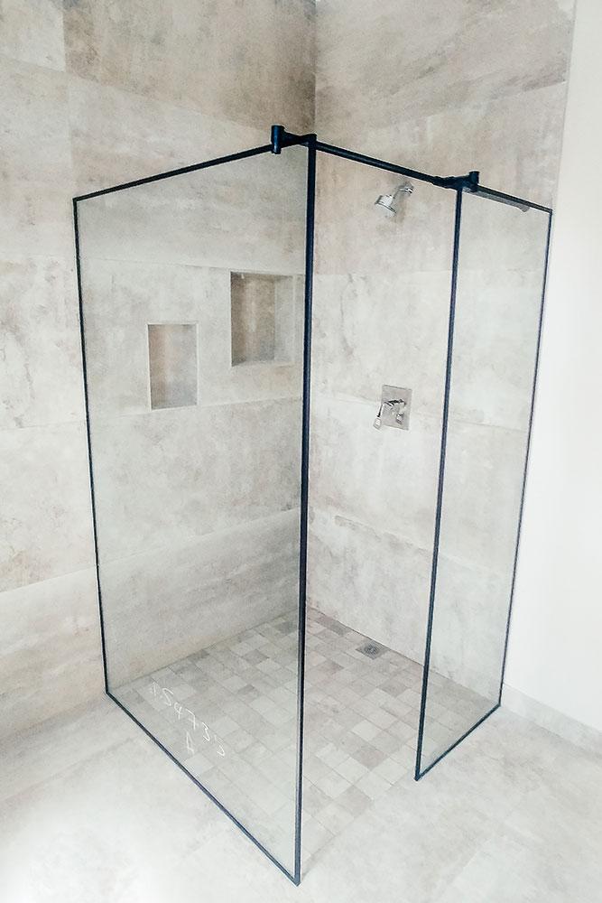 White bathroom with black framed shower and white tiled floor