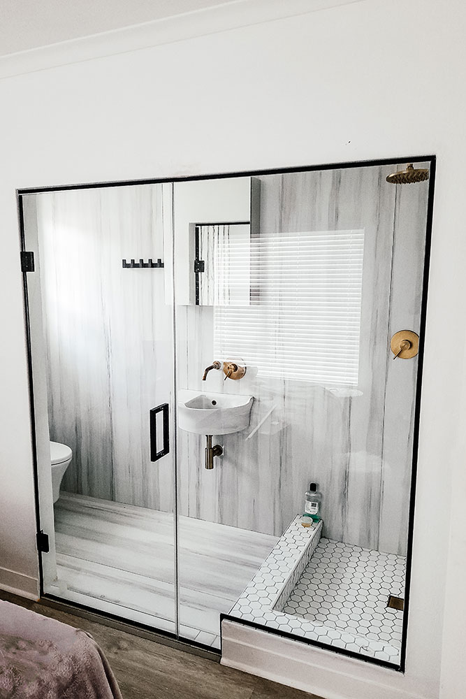 White wooden room with modern sink and honeycomb patterned framless shower