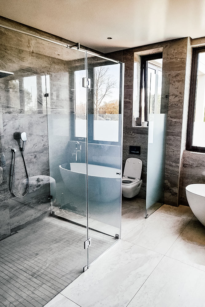 Brown and white bathroom with patterned walls and semi frameless shower