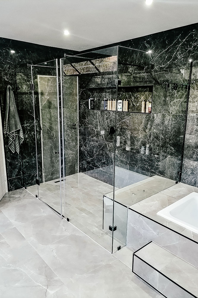 White and black bathroom with bath and frameless shower