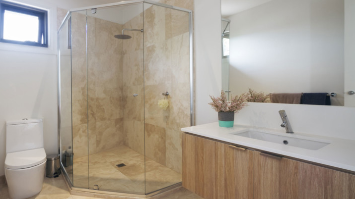 White and wooden bathroom with semi-frameless shower enclosure